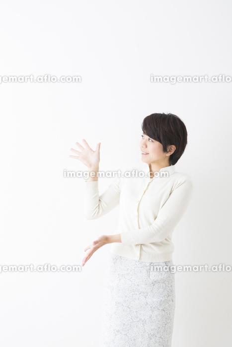 案内のポーズで立つ女性