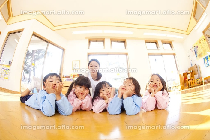 頬杖をついて微笑む幼稚園児と笑顔の幼稚園教諭の販売画像