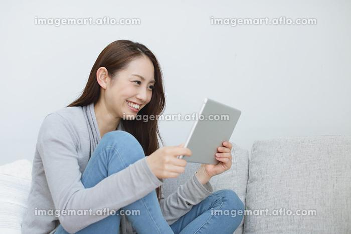 ソファーでタブレットを操作する日本人女性