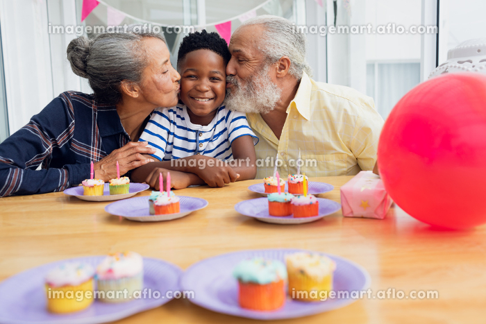 Front view of senior African-American man and woman kissing their grandson for his birthday party. Authentic Senior Retired Life Conceptの販売画像