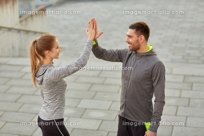 happy couple giving high five outdoors