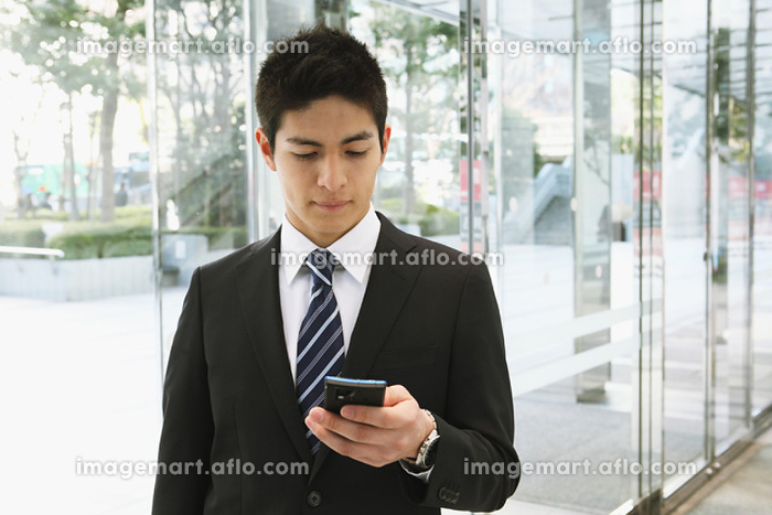 携帯を見るビジネスマン