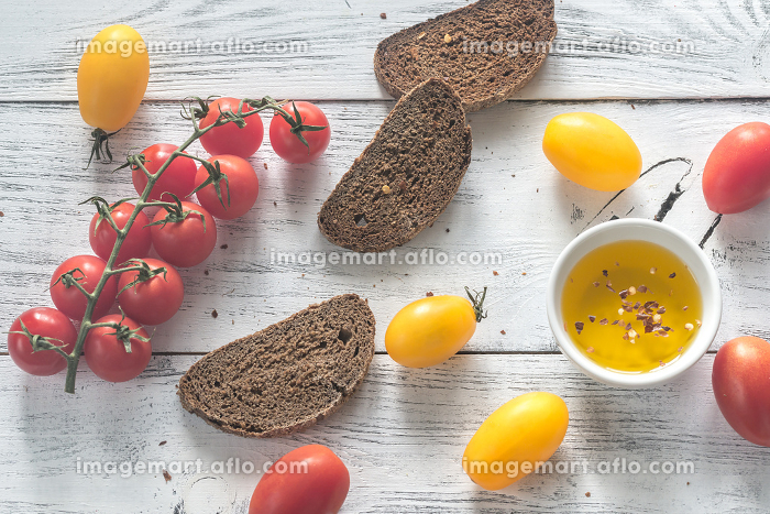 Fresh tomatoes with slices of dark-rye breadの販売画像