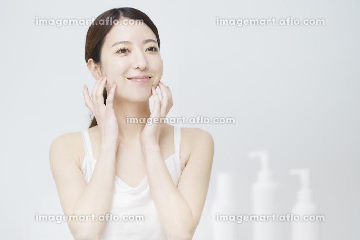 顔を触ってスキンケアをする女性と白いボトルの販売画像