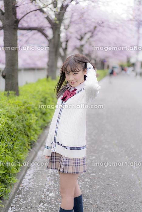 桜の木の下で髪をかきあげる女子高生