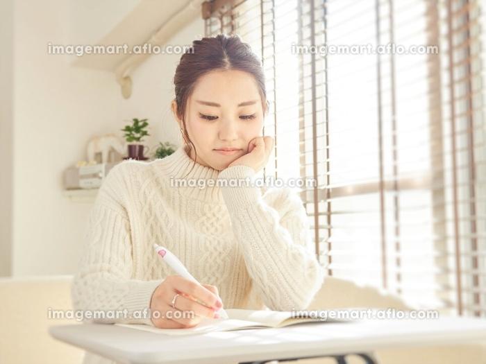 学校の課題をするアジア人女性の販売画像