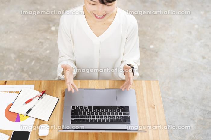 パソコンの画面に向かって話しかける女性の販売画像