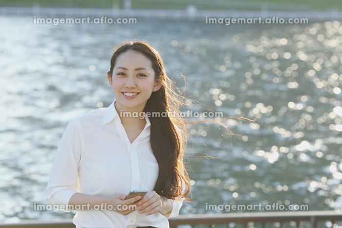 川沿いで佇む日本人ビジネスウーマン