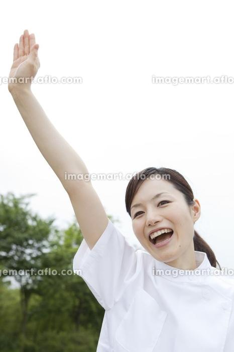 手をあげる女性介護士の販売画像