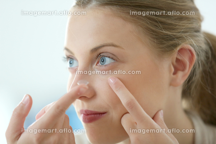 Young woman putting eye contact lense onの販売画像