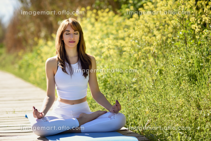 Young woman doing yoga in nature. Female wearing white sport clothes in lotus figure.の販売画像