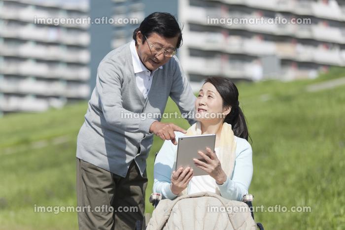 タブレットPCを見て話すシニア夫婦の販売画像