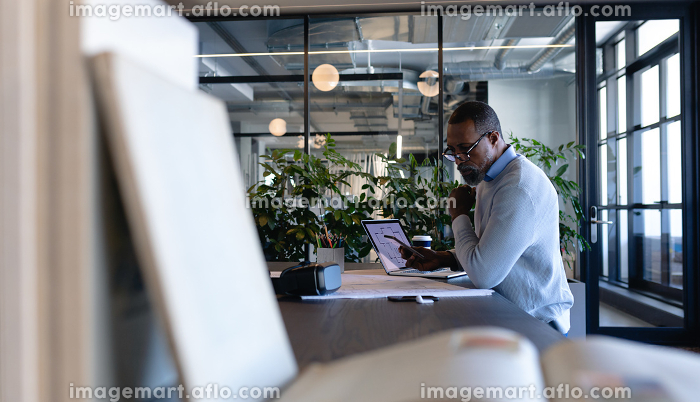 Side view of an African American businessman working in the modern office, sitting by a desk and using his smartphone. Social distancing and self isolation in quarantine lockdown