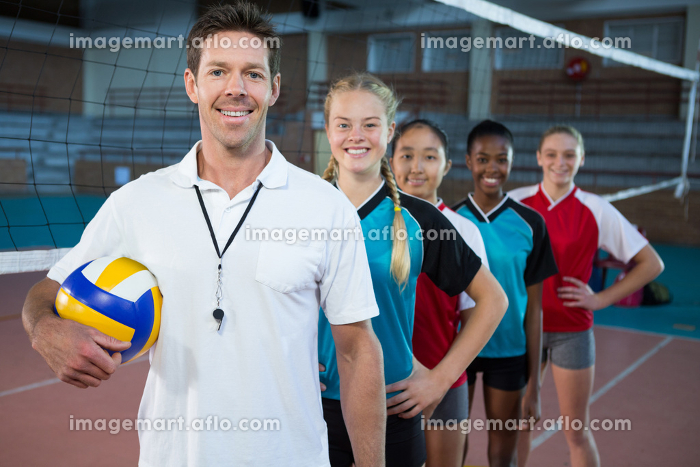 Male coach and volleyball players standing in a rowの販売画像