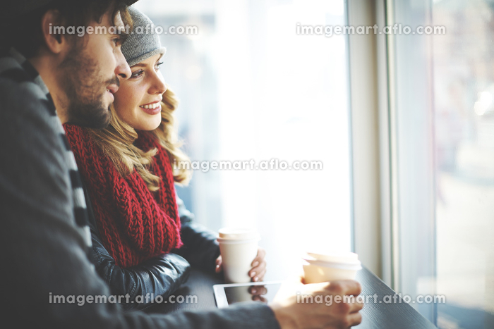 コーヒーを飲みながら窓の外を眺める外国人カップルの販売画像