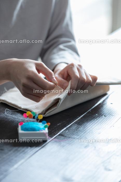 部屋の中で裁縫をする若い女性の手元の販売画像
