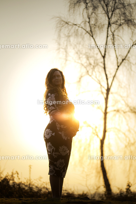 A pregnant female with red hair stood in front of a tree and sunsetの販売画像