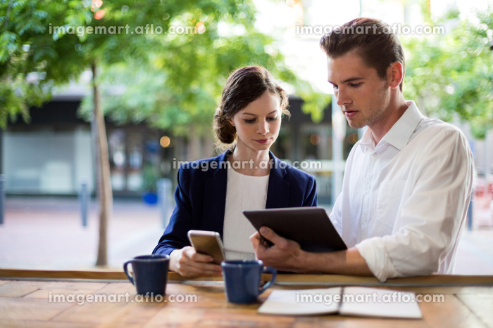 Businesspeople discussing over digital tablet at counter