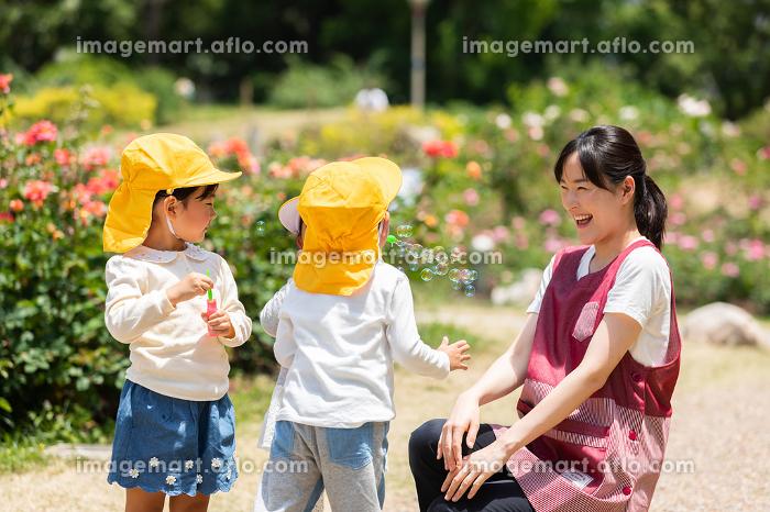 公園で遊ぶ保育士と園児