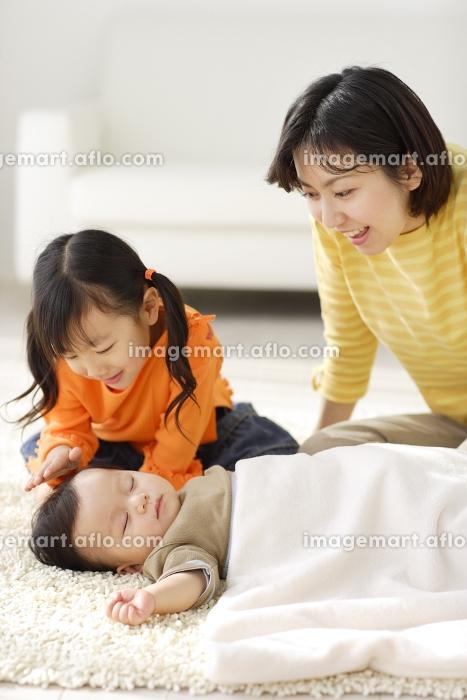 昼寝をする赤ちゃんを見守るお姉ちゃんとお母さんの販売画像