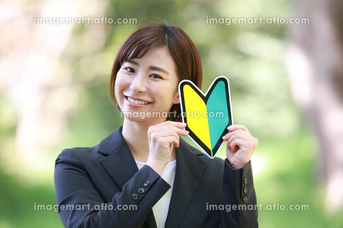 初心者マークを持つ女性社員の販売画像