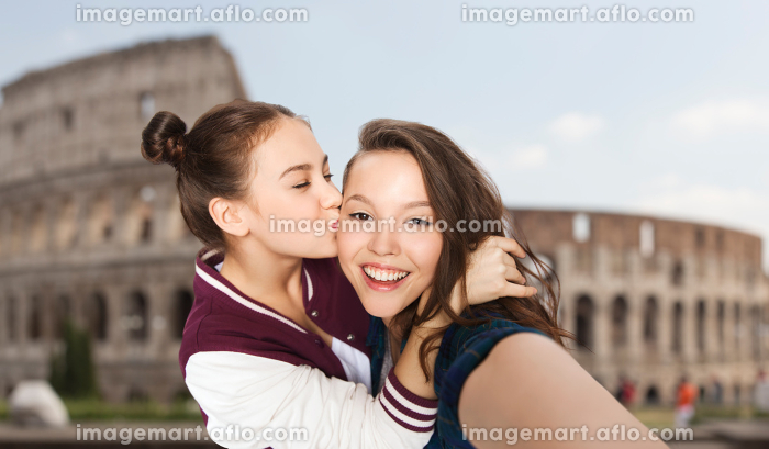happy teenage girls taking selfie over coliseumの販売画像