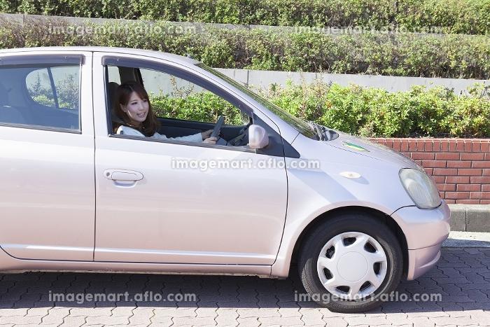 初心者マークを貼って運転する女性の販売画像
