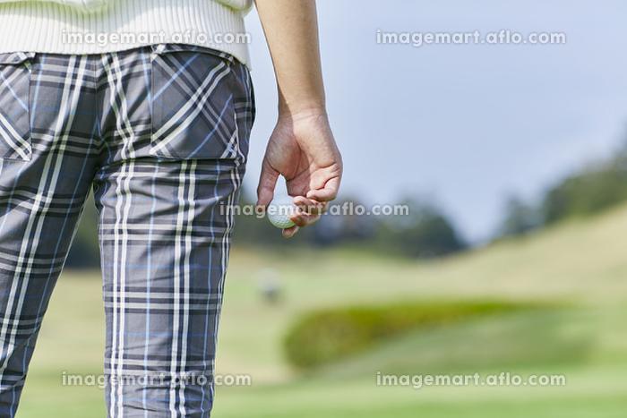 ゴルフボールを持つ日本人男性