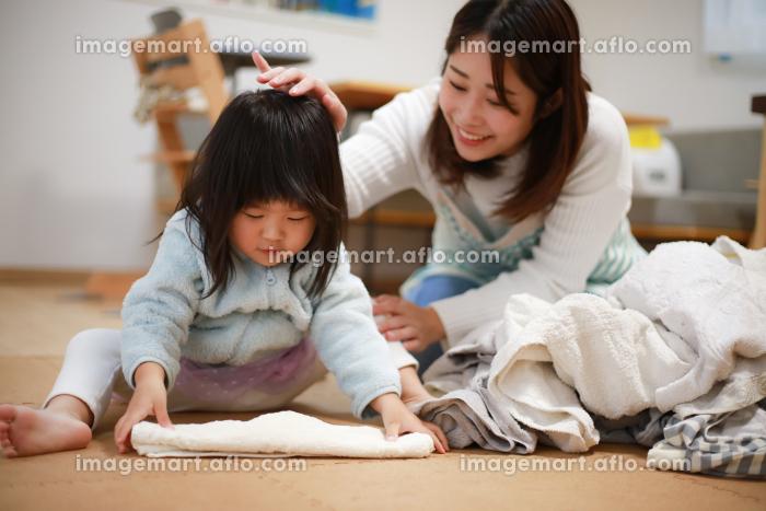 洗濯物をたたむ手伝いをする女の子の販売画像