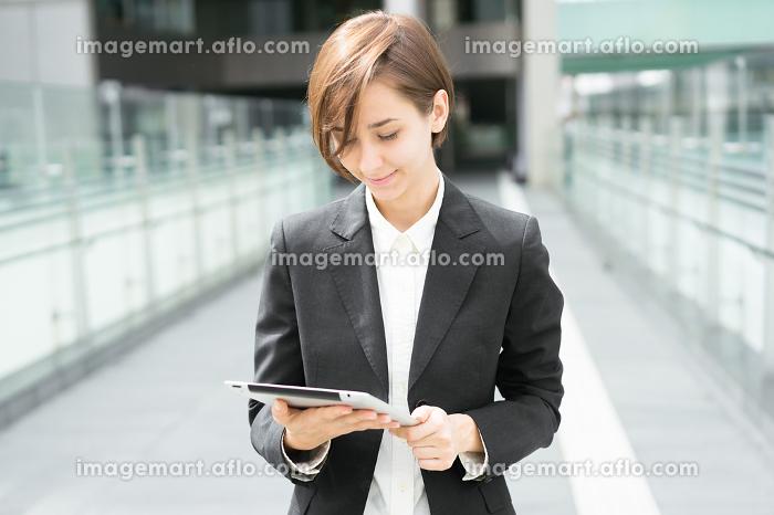 タブレットPCを持ってビジネス街を歩く女性の販売画像