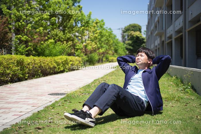 芝生の上で腹筋運動をする男性の販売画像