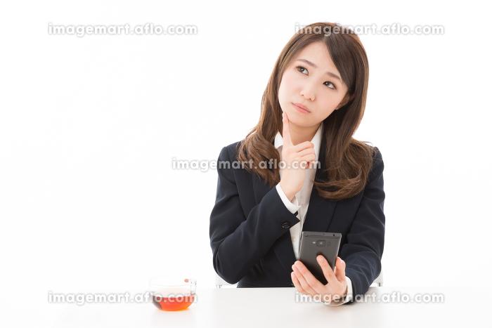 スマホを見る女性 ビジネス 考えるの販売画像