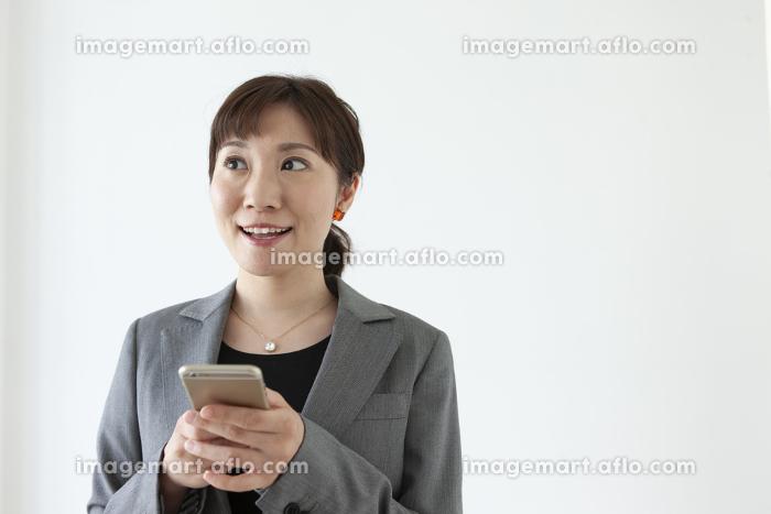 スマートフォンを持っているビジネスウーマンの販売画像