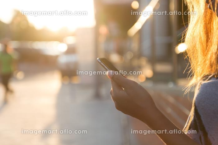 closeup women using smartphone at sunsetの販売画像