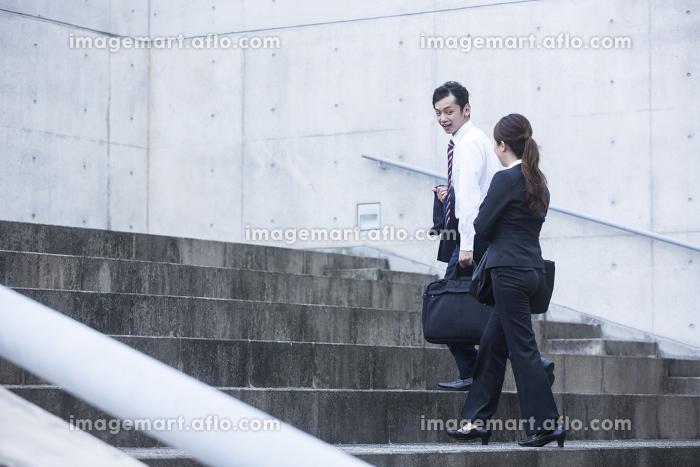 階段を上るビジネスマンとビジネスウーマン