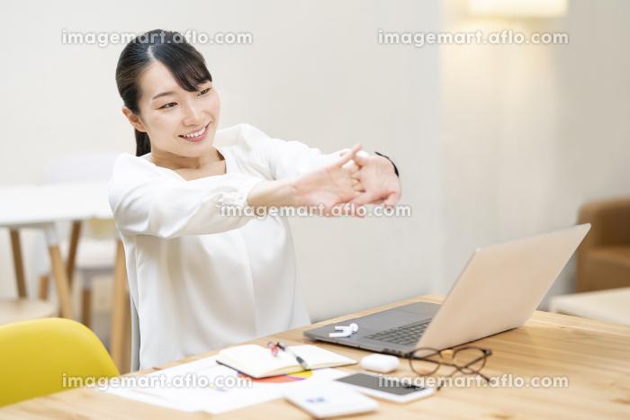 カジュアルな空間での仕事中のストレッチする女性の販売画像