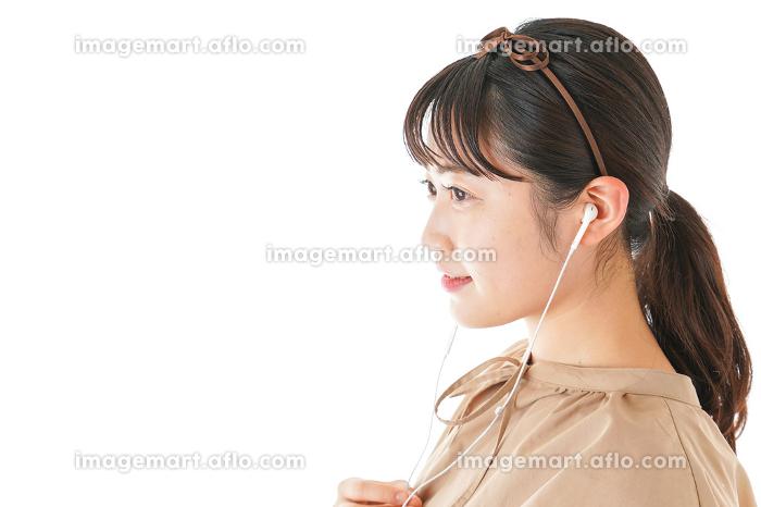 イアフォンで音楽を聞く若い女性の販売画像