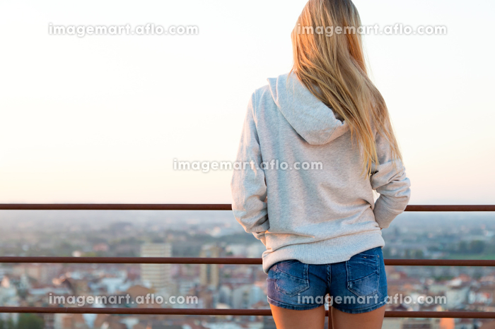 Beautiful blonde stands on the edge of the roof.の販売画像