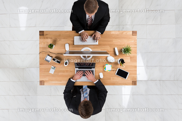 Businessmen Using Laptop And Computer At Desk In Officeの販売画像