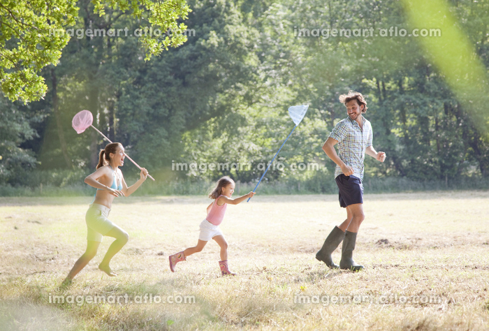 Family in countryside running with netsの販売画像