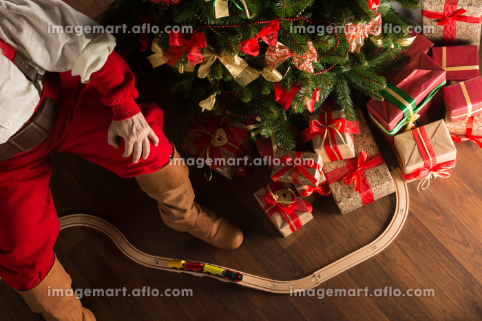 Unrecognizable Santa Claus playing with wooden railroad near Christmas tree. Top view indoors at dark roomの販売画像