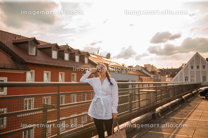 Young woman in white blouse standing and leaning on fenceの販売画像
