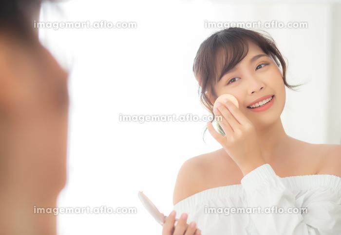 Portrait beautiful young asian woman applying powder puff at cheの販売画像