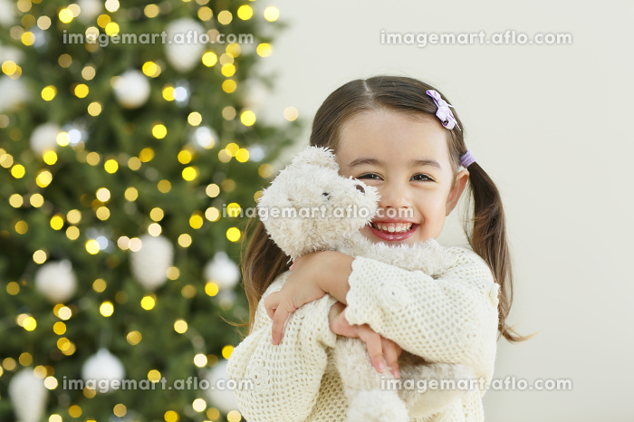 クリスマスツリーとぬいぐるみを抱いた小さな女の子