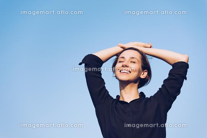 青空の下でリラックスをする女性の販売画像