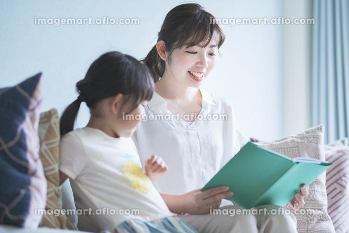 ソファに座って絵本を読む親子の販売画像