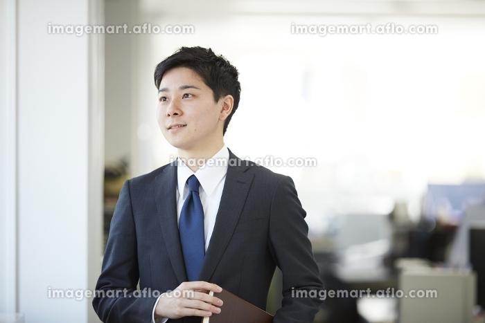 オフィスから外を眺める日本人サラリーマンの販売画像
