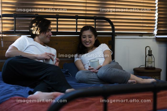 ベッドで談笑する若いカップルの販売画像