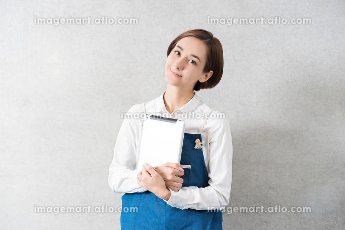 エプロン姿でタブレットPCを持つ女性の販売画像
