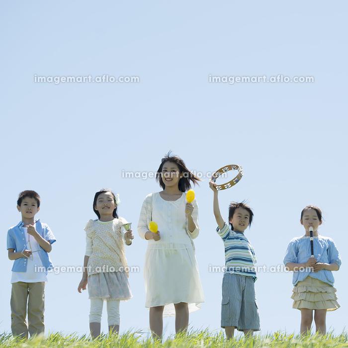 草原で楽器を持ち微笑む小学生と先生の販売画像